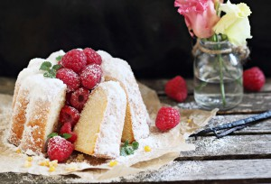Vanilla cake with fresh raspberries on a rustic dark background