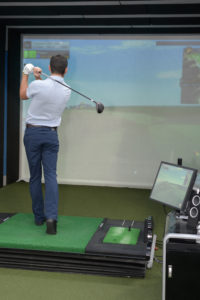 Man practicing golf on indoor simulator