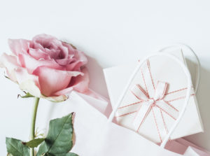 Pink pstel rose, light paper bag and light gift box with a bow on a white background. Gentle romantic wedding or womens day headline. Wide banner spring sale, desaturated colors top view.